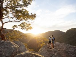 Couple watching a scenic sunset over the Hawkesbury Valley from the Vale of Avoca lookout in Grose Vale