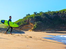 A surfer is about to enter the water at Werri Beach in Gerringong, Kiama Area.