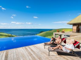 Couple relaxing by the pool at Ocean Farm luxury accommodation in Gerringong.