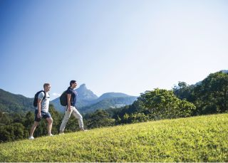 Couple enjoying a walk through the 25 acres of farm nestled at the base of Wollumbin-Mt Warning