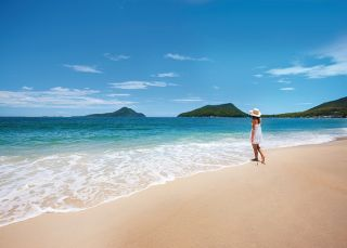 Woman enjoying views of Mount Tomaree from Shoal Bay in Port Stephens