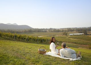 A couple enjoying a picnic at Audrey Wilkinson in Pokolbin, Hunter Valley