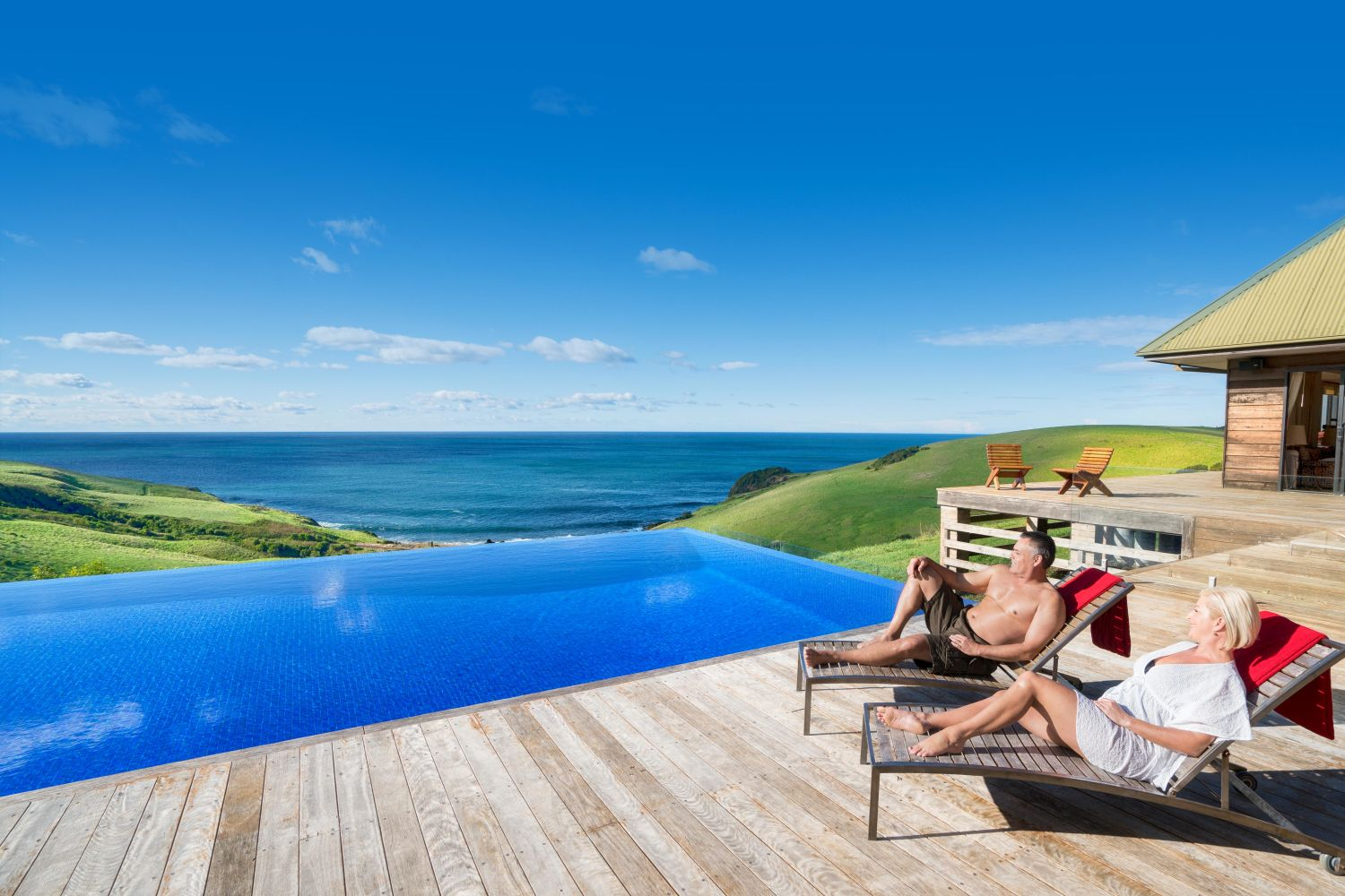 Couple relaxing by the pool at Ocean Farm in Gerringong, Kiama Area, South Coast NSW