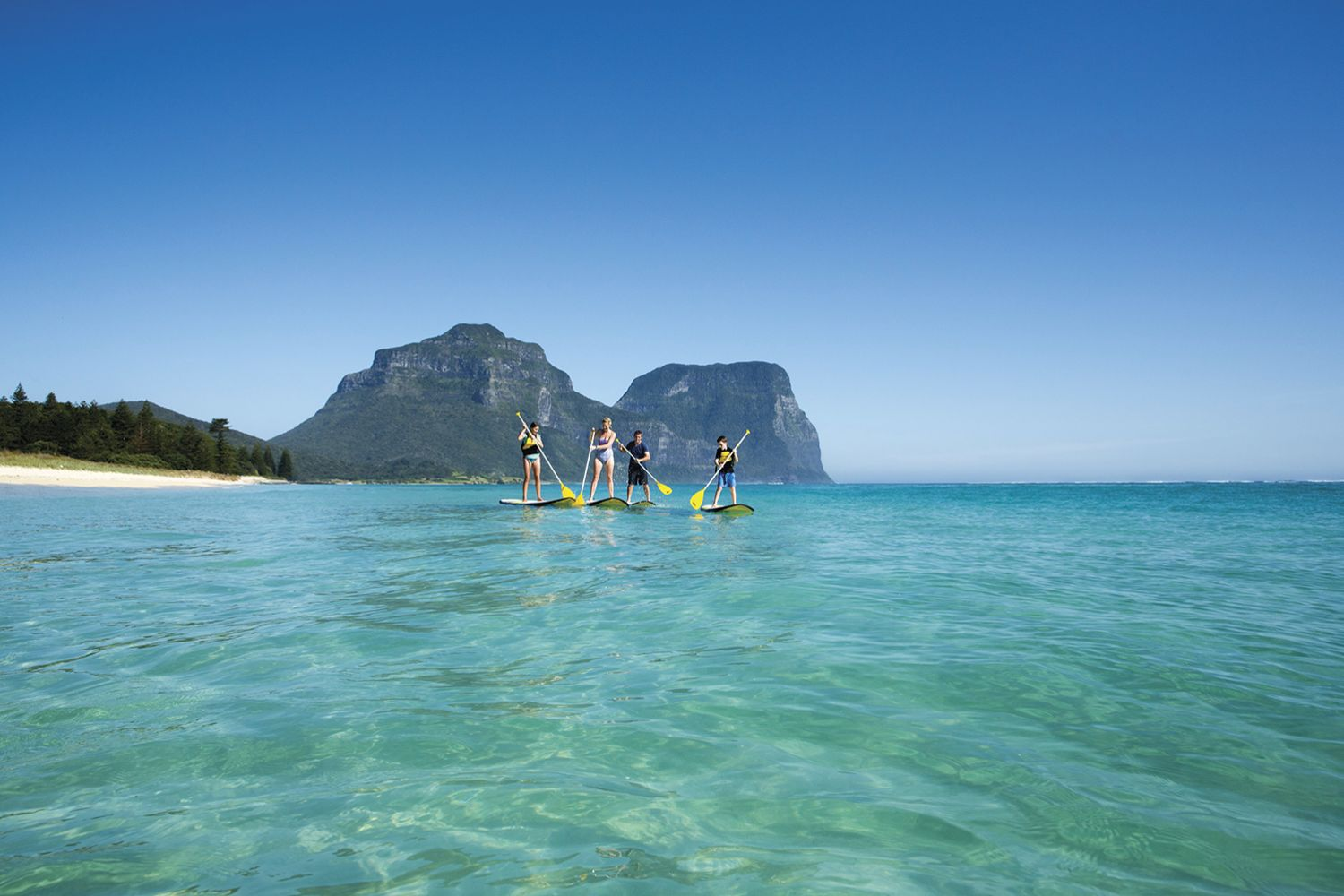 Family stand-up paddleboarding at Lagoon Beach on Lord Howe Island with Mount Gower and Mount Lidgbird as the backdrop