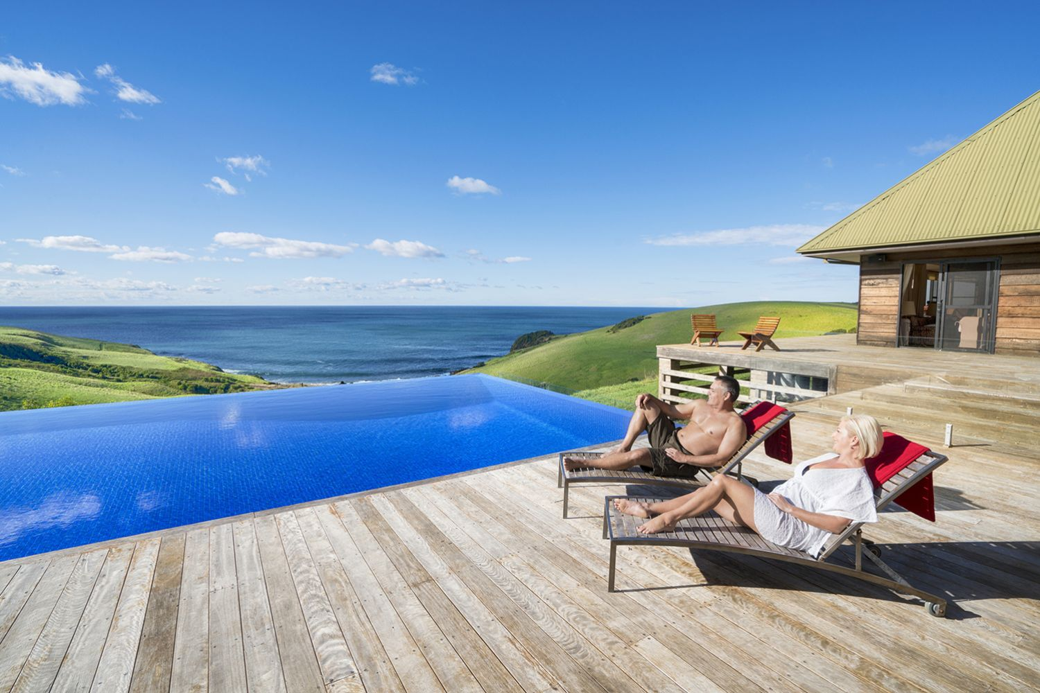 Couple relaxing by the pool at Ocean Farm luxury accommodation in Gerringong