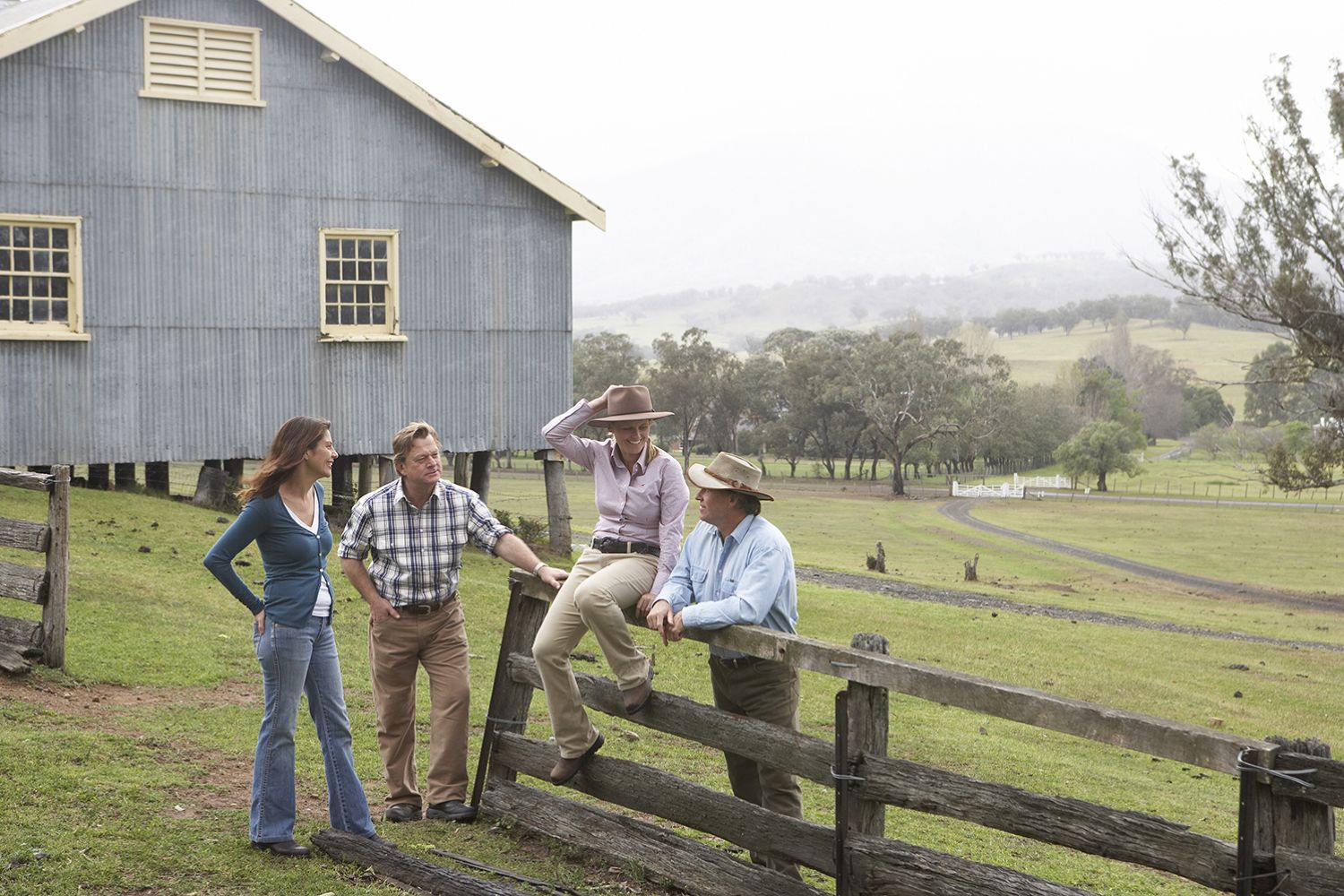 Small group of people relaxing at the fence gate near the shearing sheds at Belltrees Estate in Scone, Upper Hunter