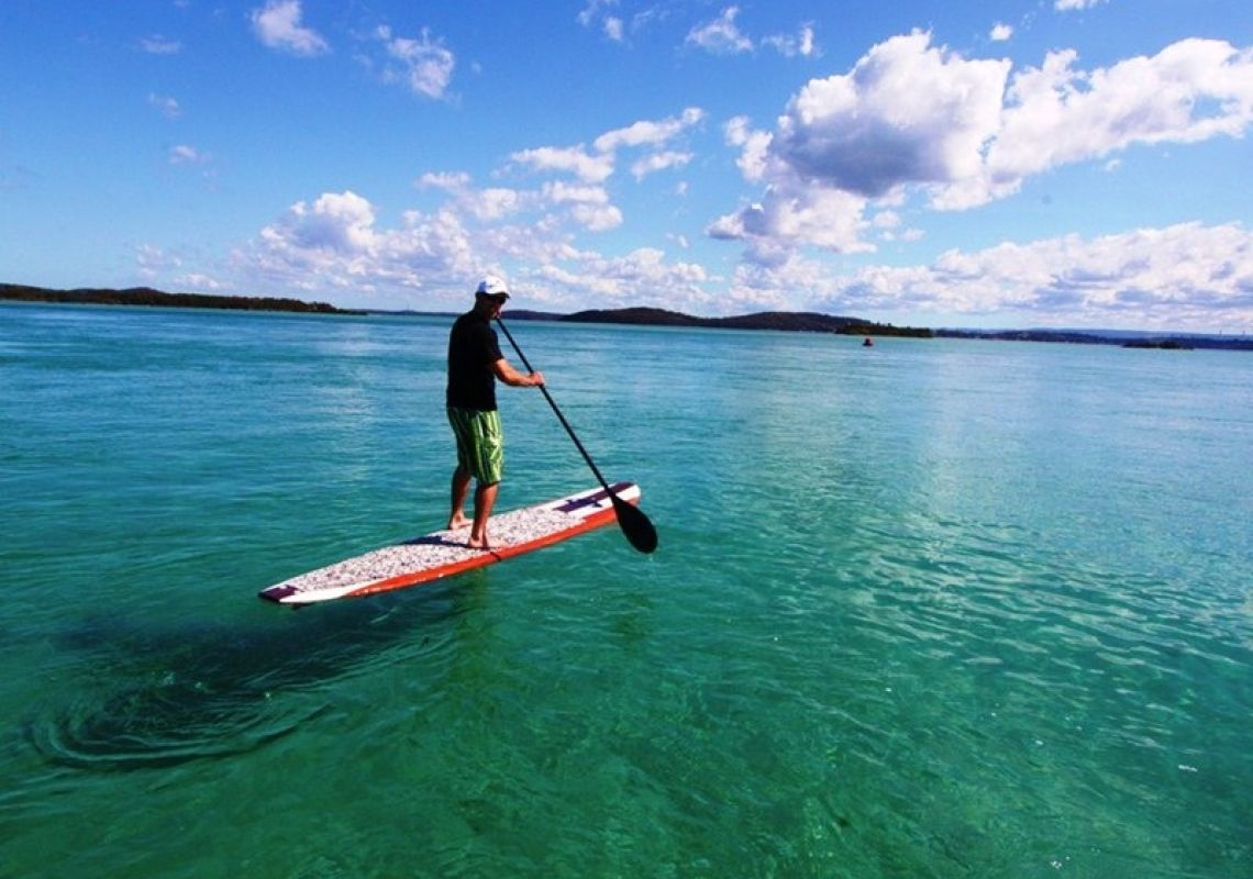 Man on a Lake Mac-hired stand-up paddleboard on Lake Macquarie