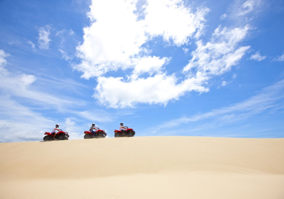 Quad bikes tour the Stockton Bight sand dunes in Port Stephens, NSW
