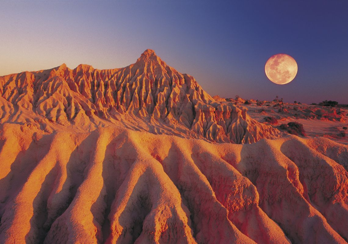 A full moon shines over the Walls of China sand formation in Mungo National Park, Outback NSW, Australia