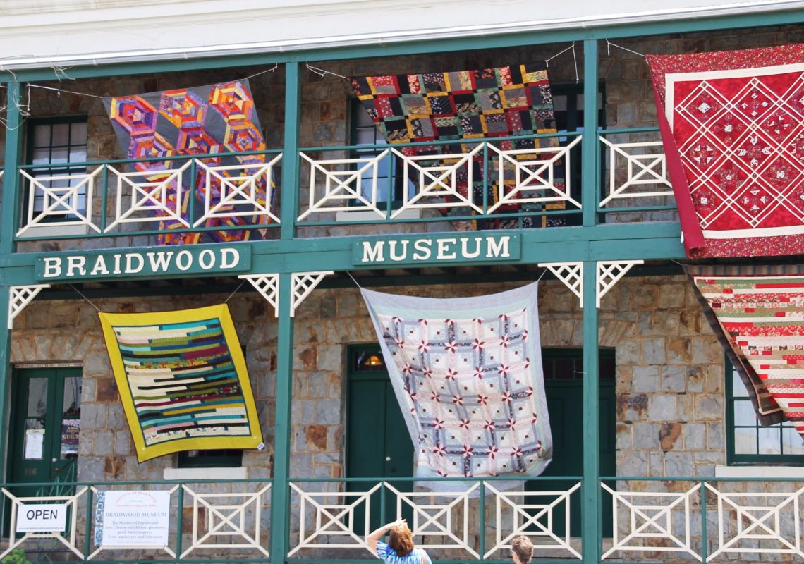 Quilts over the rails of the Braidwood Museum in Braidwood