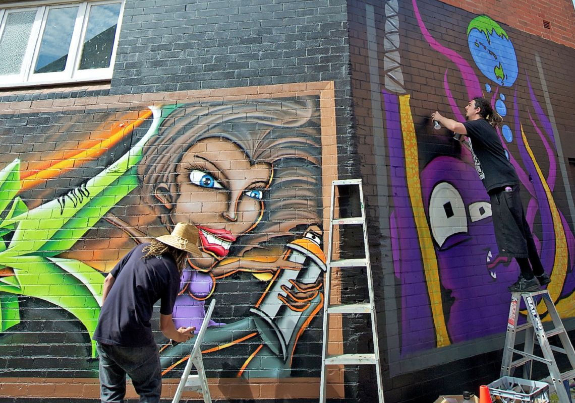 Street artists spray paint walls in The Back Alley Gallery, Lismore