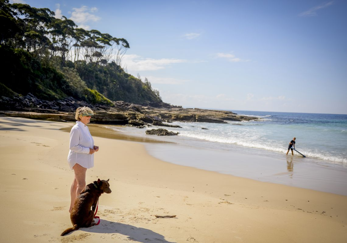 A woman and her dog on a beach, Bawley Point