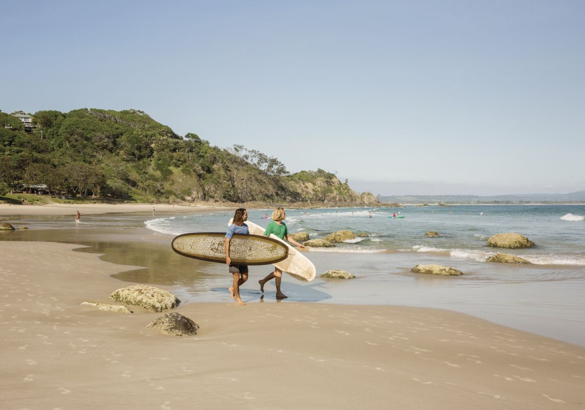 Two surfers holding their longboards survey Wategos Beach, Byron Bay
