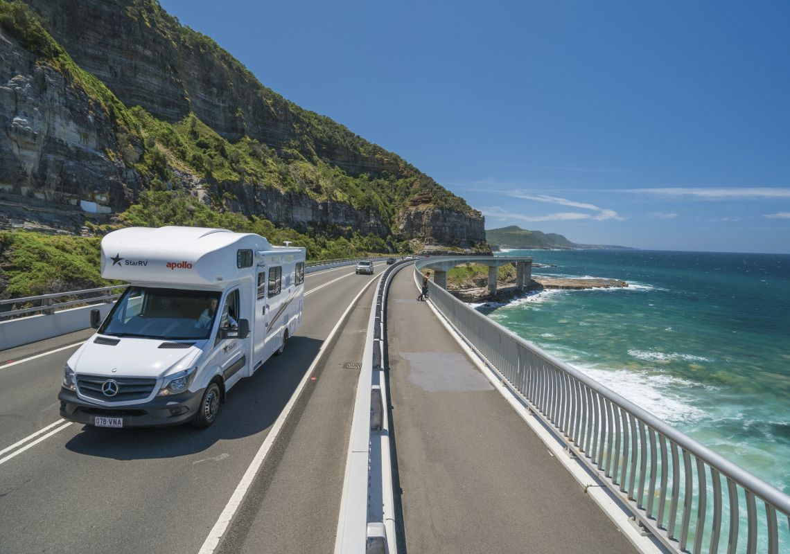 A campervan driving on the Sea Cliff Bridge, near Clifton