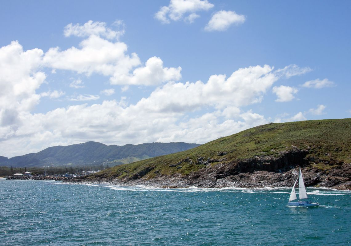 Boat sailing past Muttonbird Island Nature Reserve, Coffs Harbour