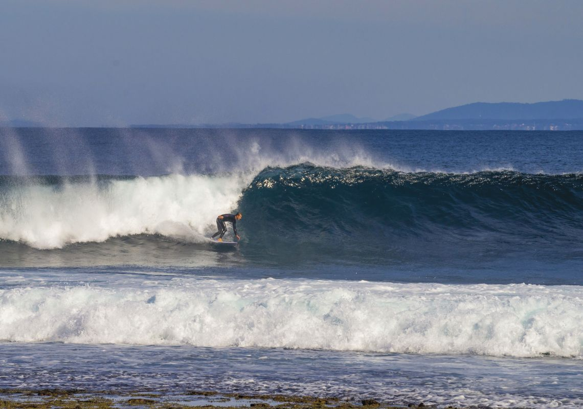 Surfer catches a wave in Jervis Bay, near Booderee National Park