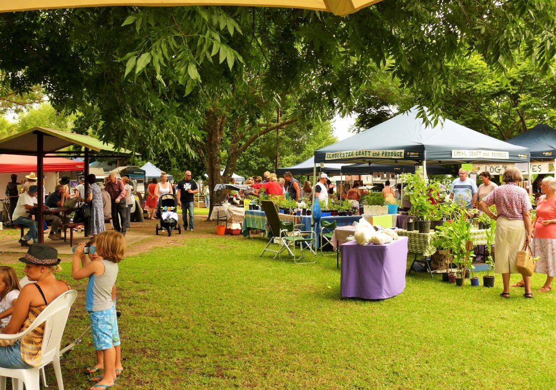 People relaxing at Gloucester Farmers Market in Billabong Park, Gloucester
