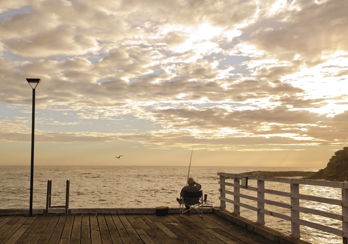 Man enjoying a relaxing day fishing off Tathra Wharf.