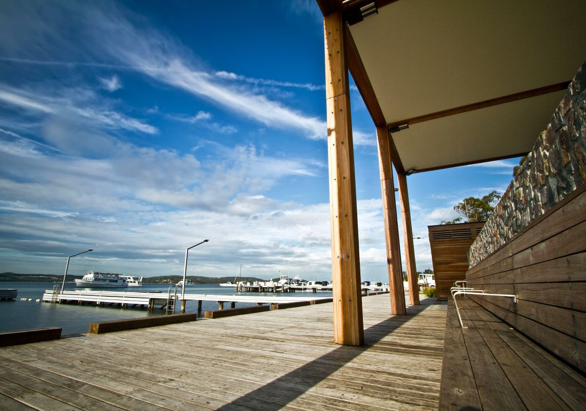 The wooden Toronto public wharf and a tour boat on Lake Macquarie