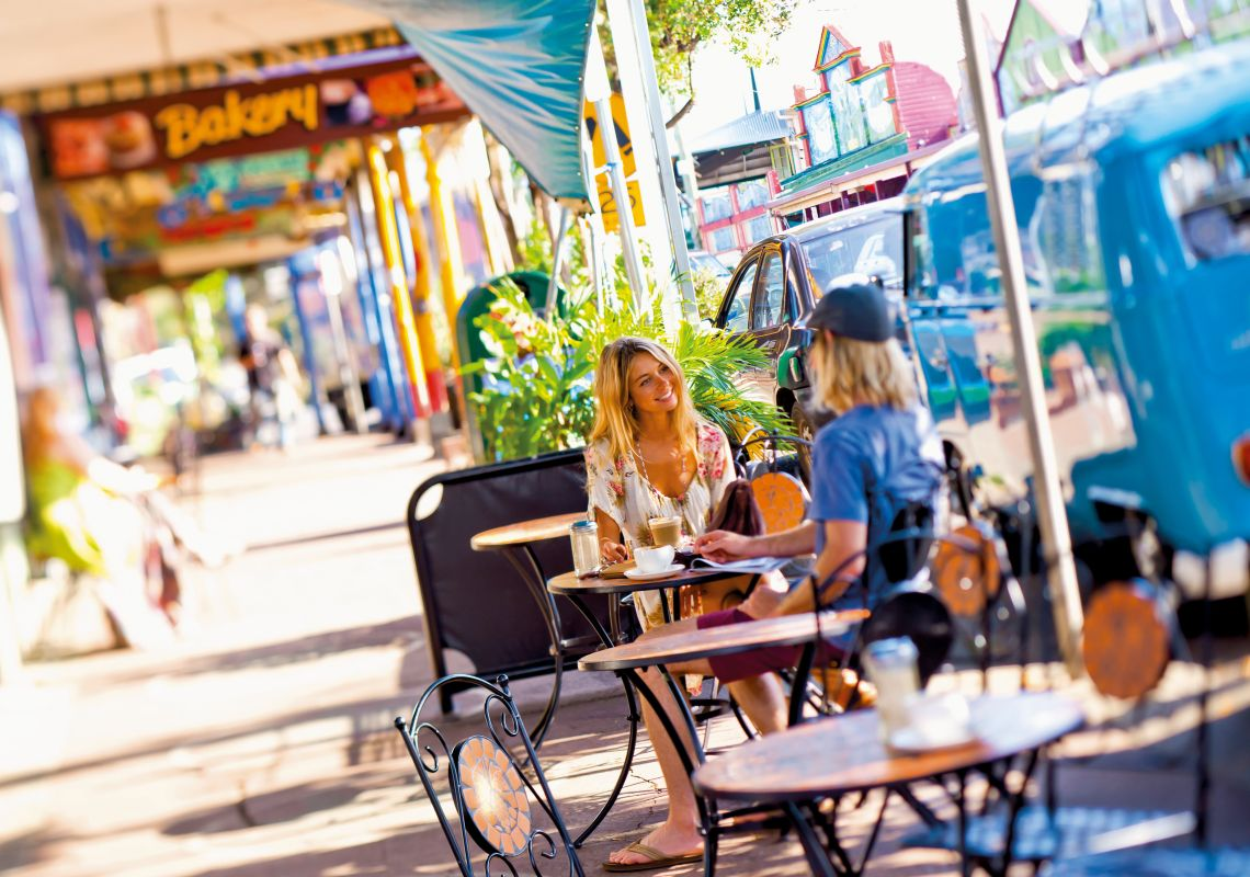 Friends chat at an alfresco cafe on Cullen Street, Nimbin