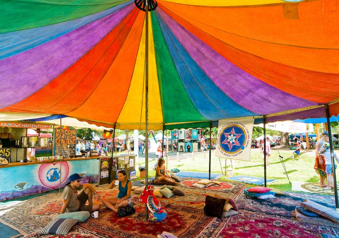 People relax under a colourful tent at Channon Craft Market, near Lismore