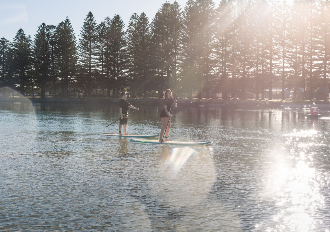 Couple stand-up paddelboarding at Lake Illawarra in Shellharbour.