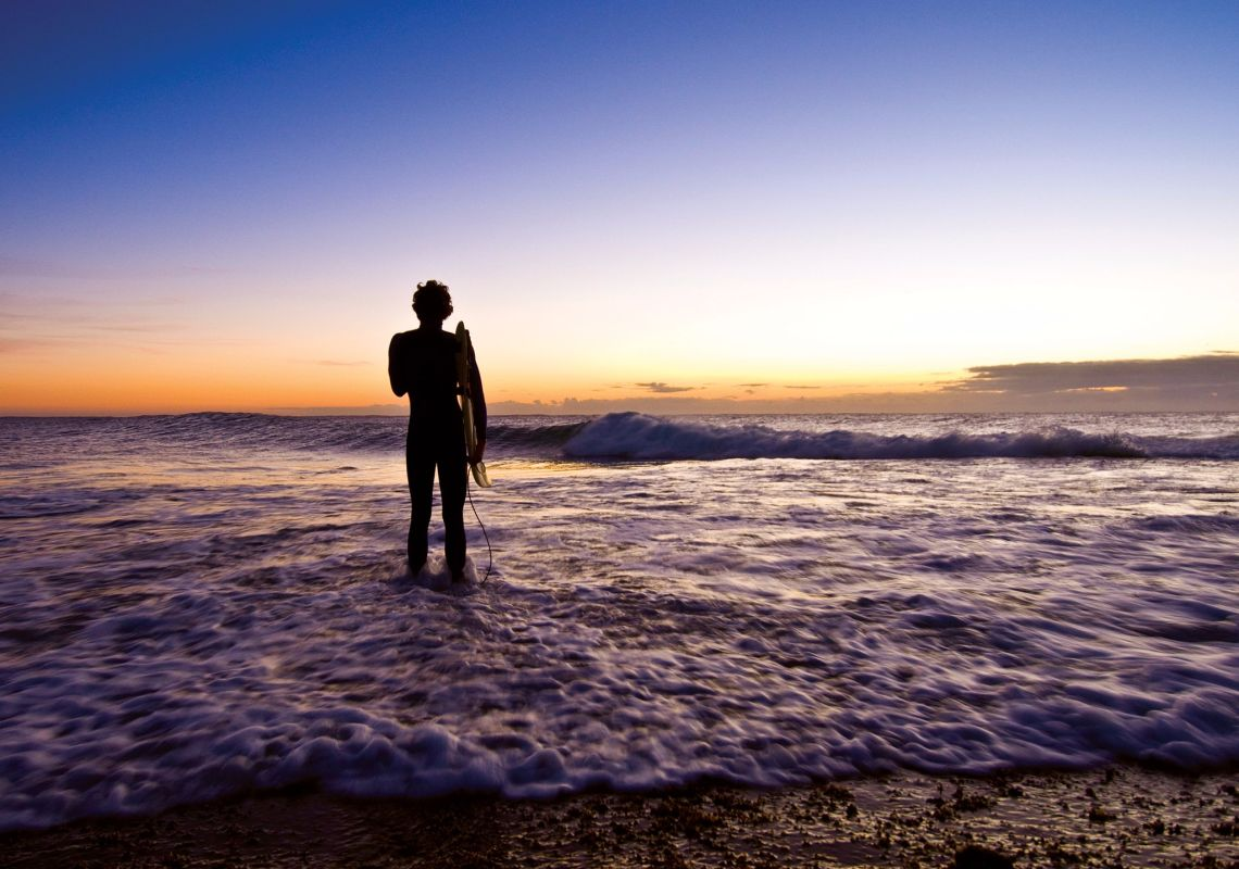 A surfer watches dawn and waves break at Angourie Point, near Yamba
