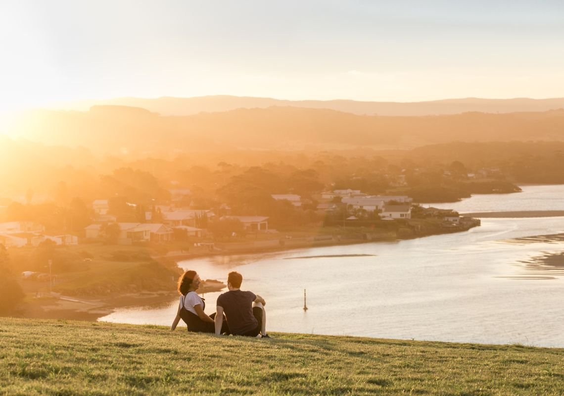 Couple enjoying sunset views on the Kiama Coast Track, NSW, Australia