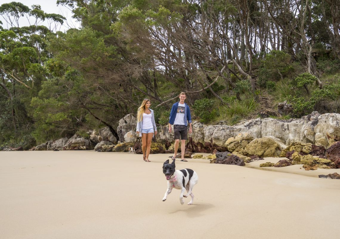 Couple walking their dog along Washerwomans Beach in Shoalhaven, NSW South Coast