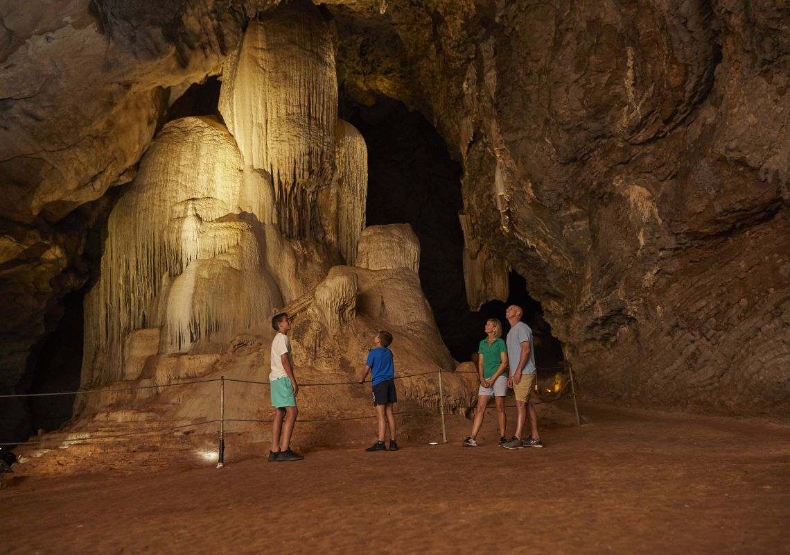 Family exploring limestone formations in the Cathedral Cave, Wellington Caves