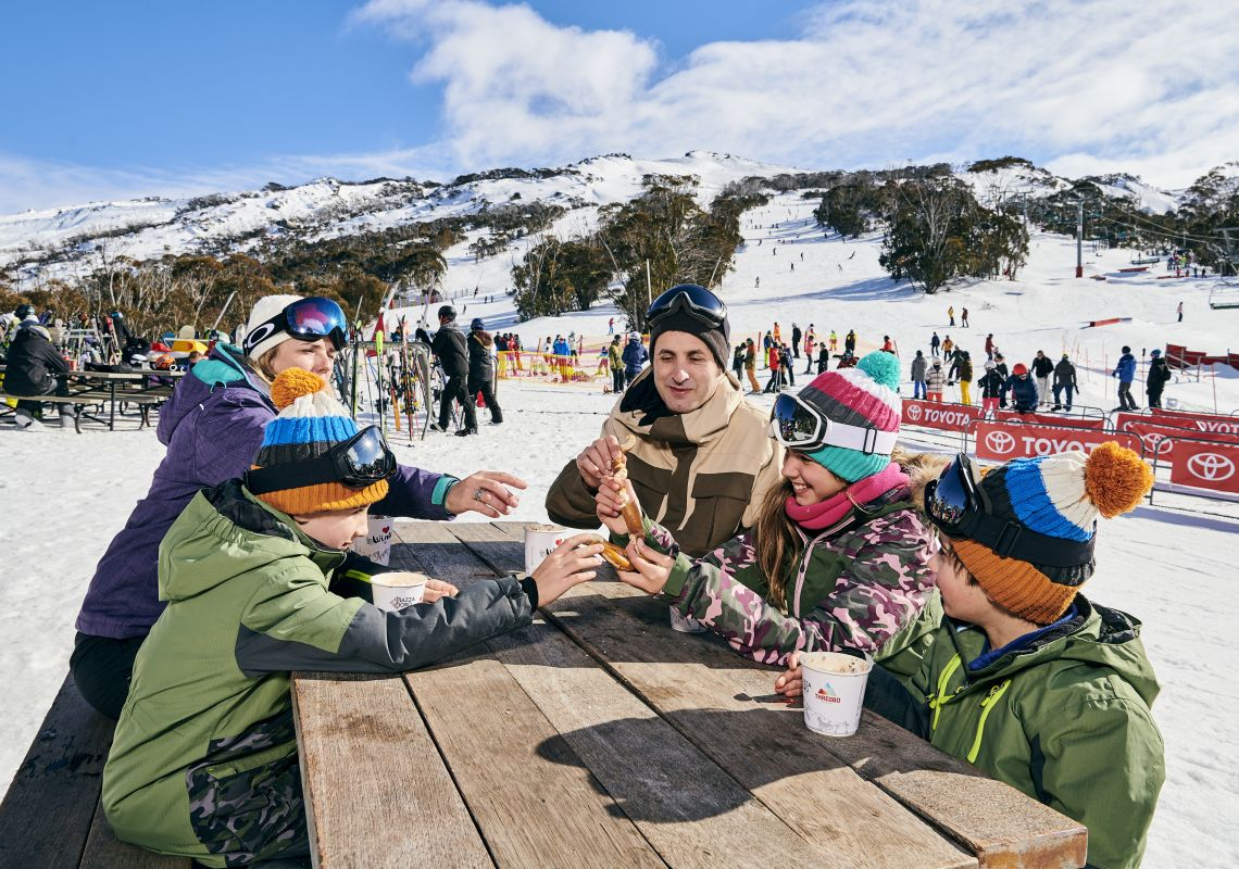 A family warming up with hot chocolates at Thredbo ski resort in the Snowy Mountains