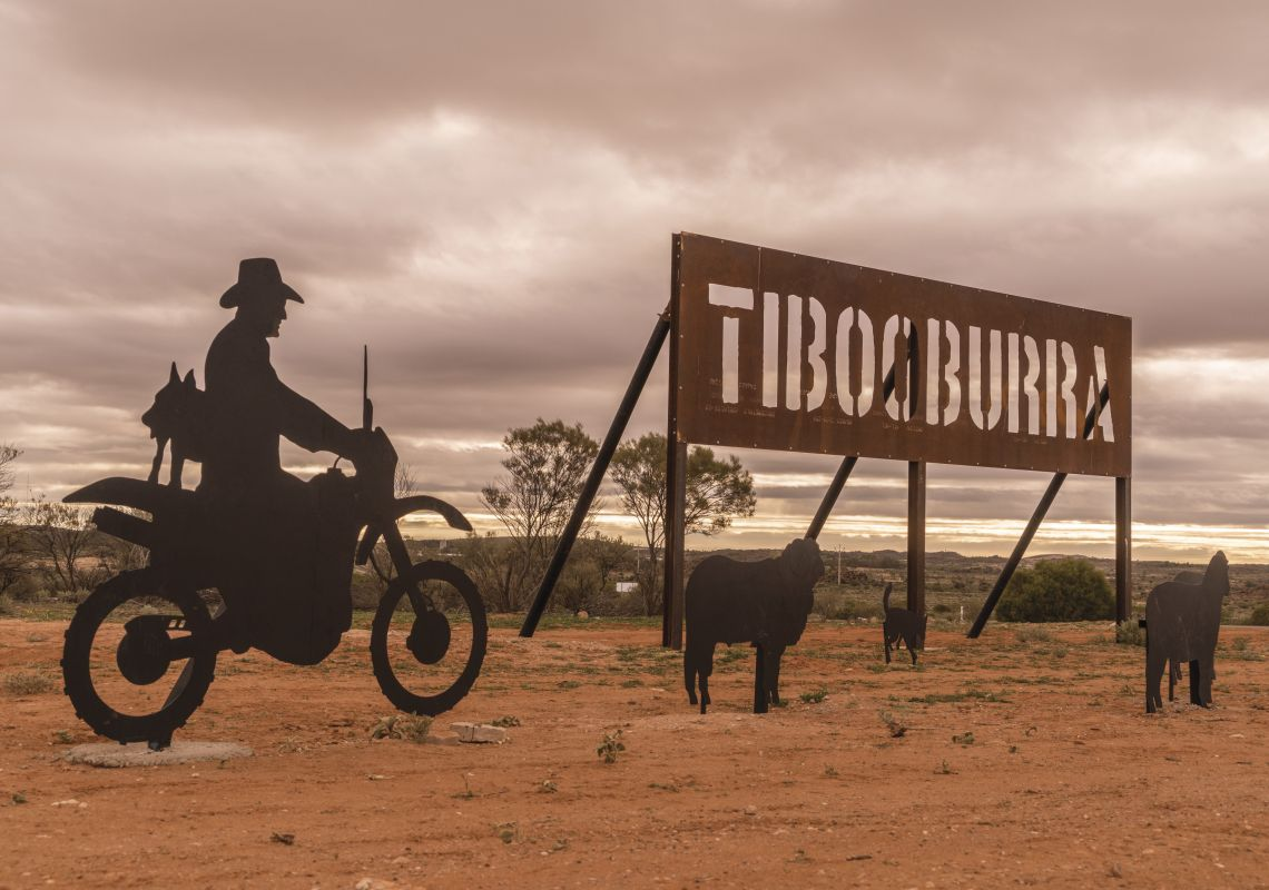 A sign and statues of sheep and a farmer on a motorbike welcome visitors to Tibooburra