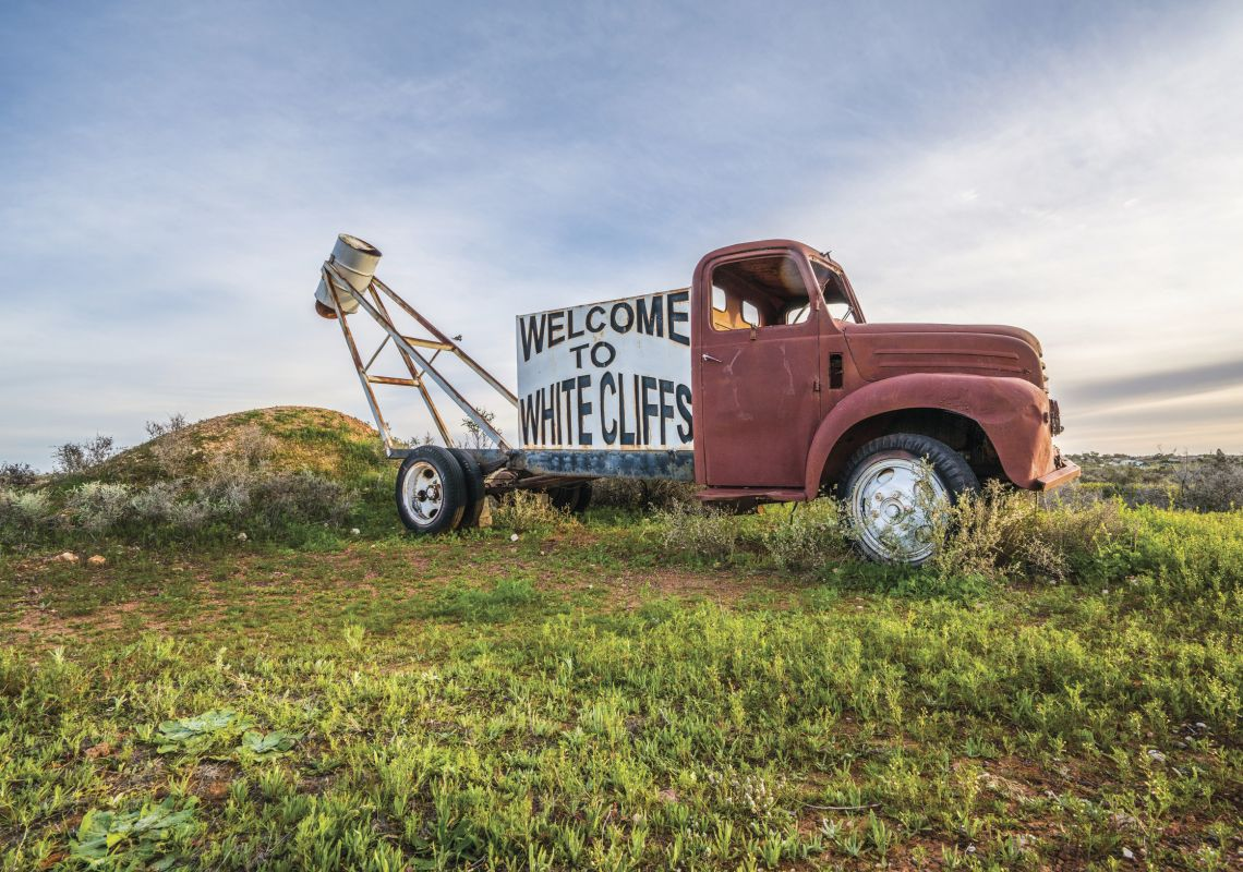 A red truck with a sign welcoming visitors to White Cliffs in Outback NSW