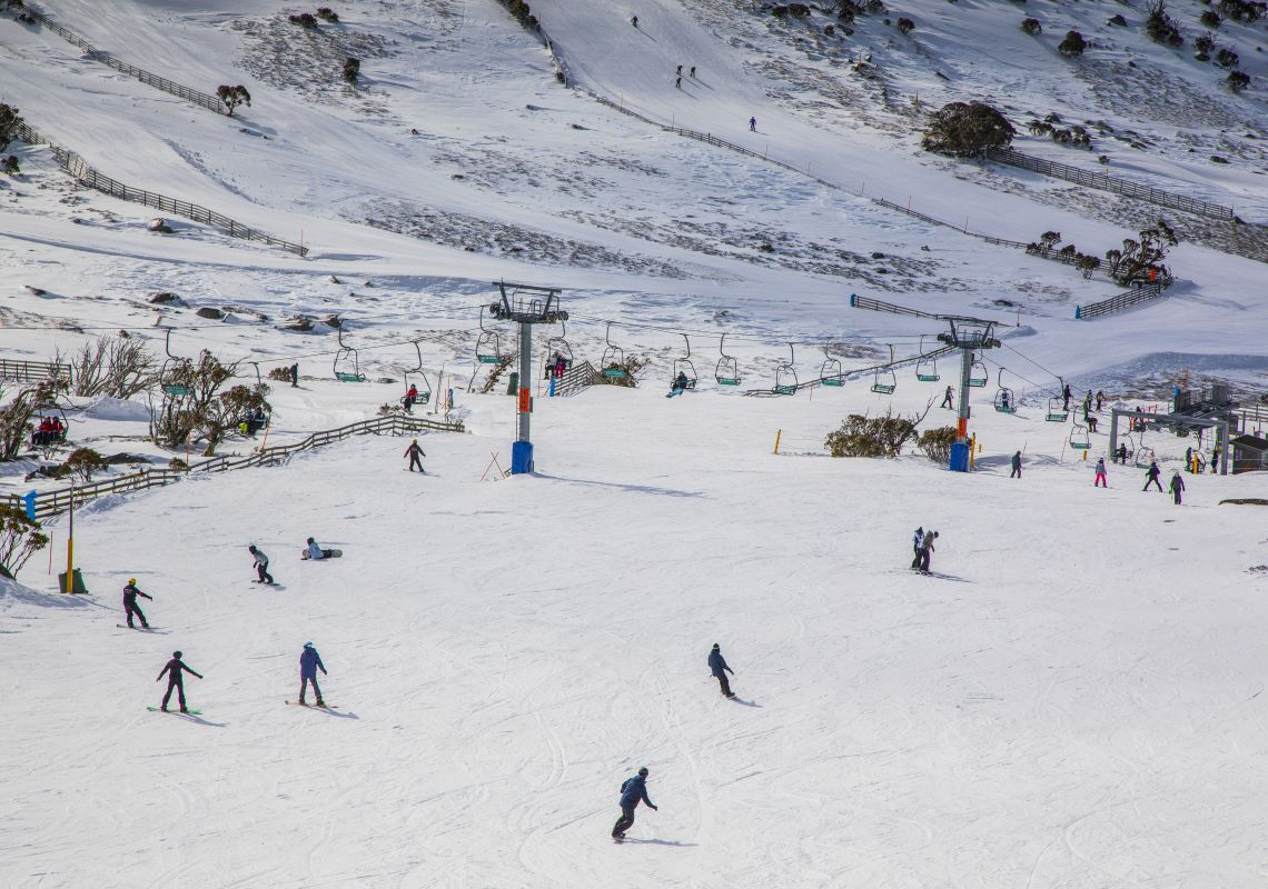People enjoying a day of skiing and snowboarding at Blue Cow ski resort in Perisher