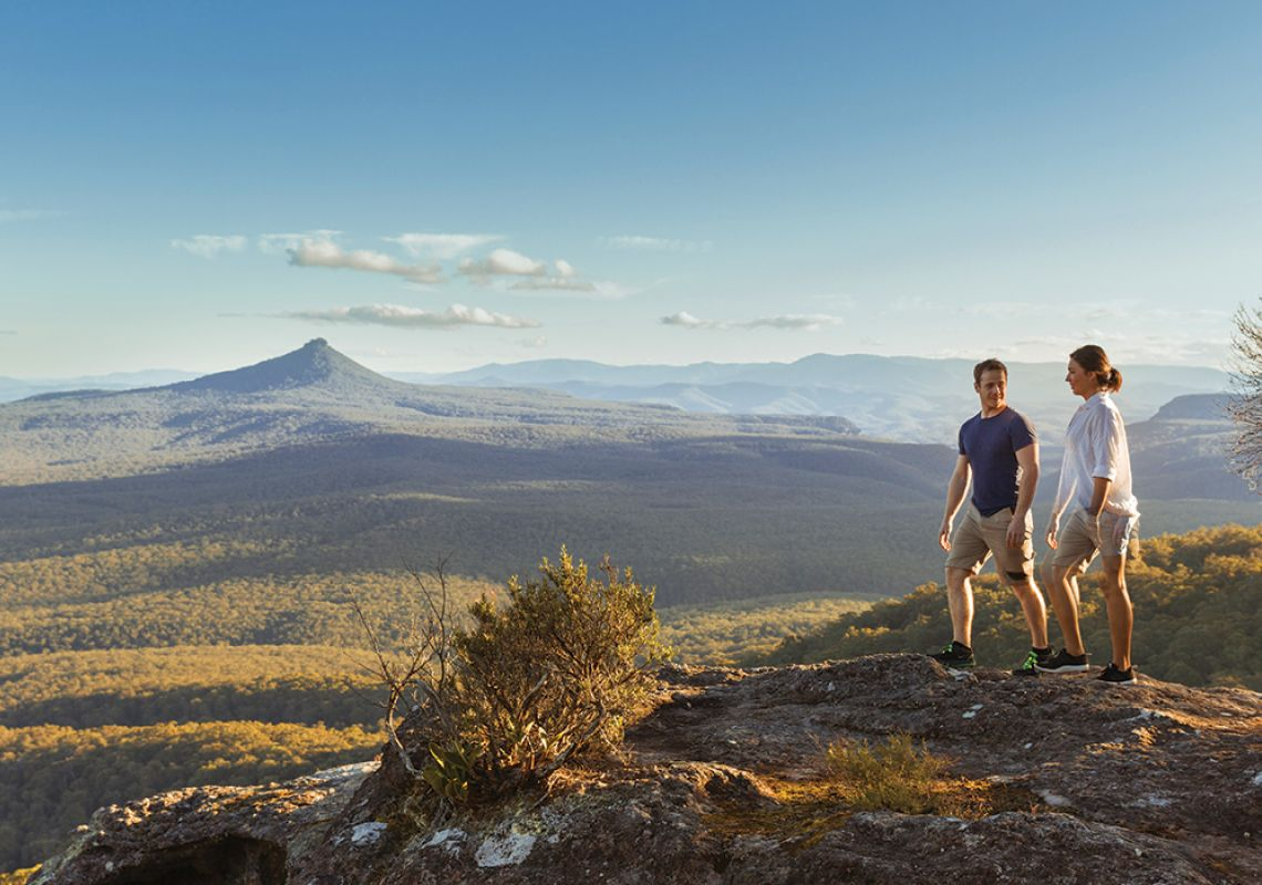 Couple hiking with views of Pigeon House Mountain, Shoalhaven