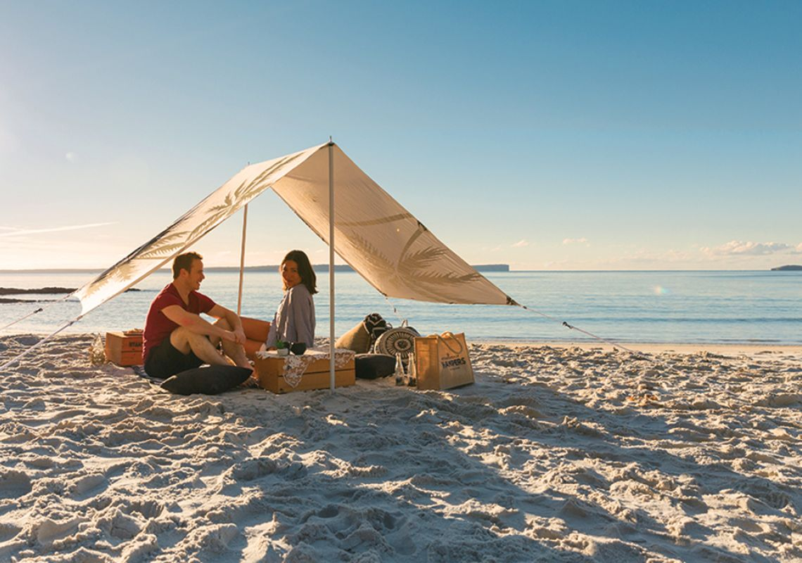 A couple enjoying a sunrise beach picnic at Blenheim Beach, Jervis Bay, South Coast