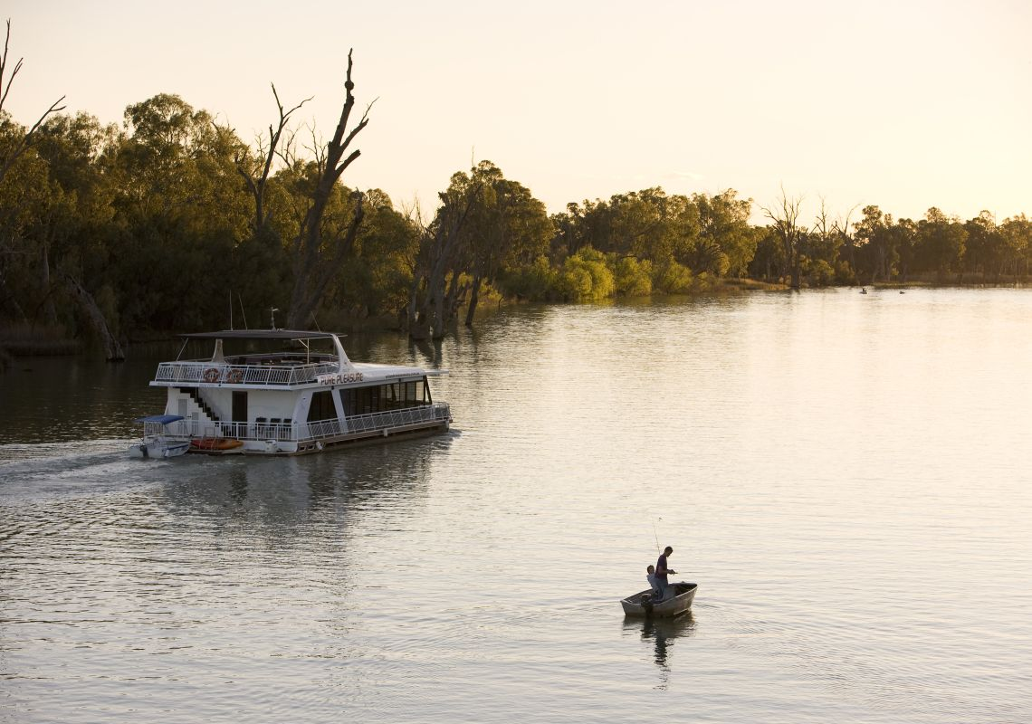 An 'All Seasons Houseboat' passes a fishing boat at sunset on the Murray river, The Murray