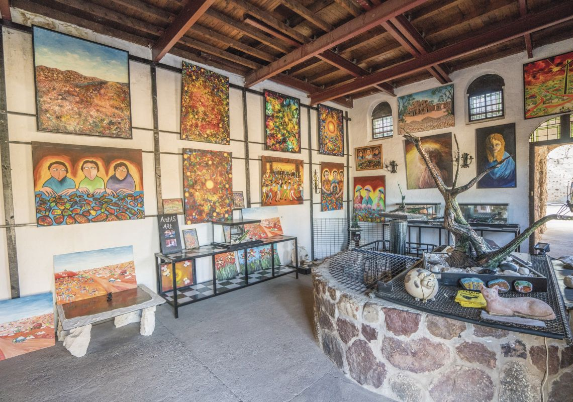 Brightly coloured paintings line the walls at Anita's Art Gallery, Lightning Ridge