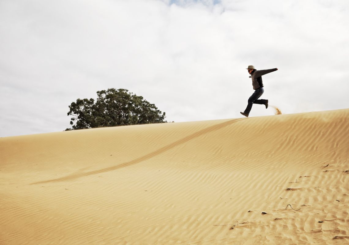 A man runs down the side of a dune at Perry Sandhills, Wentworth