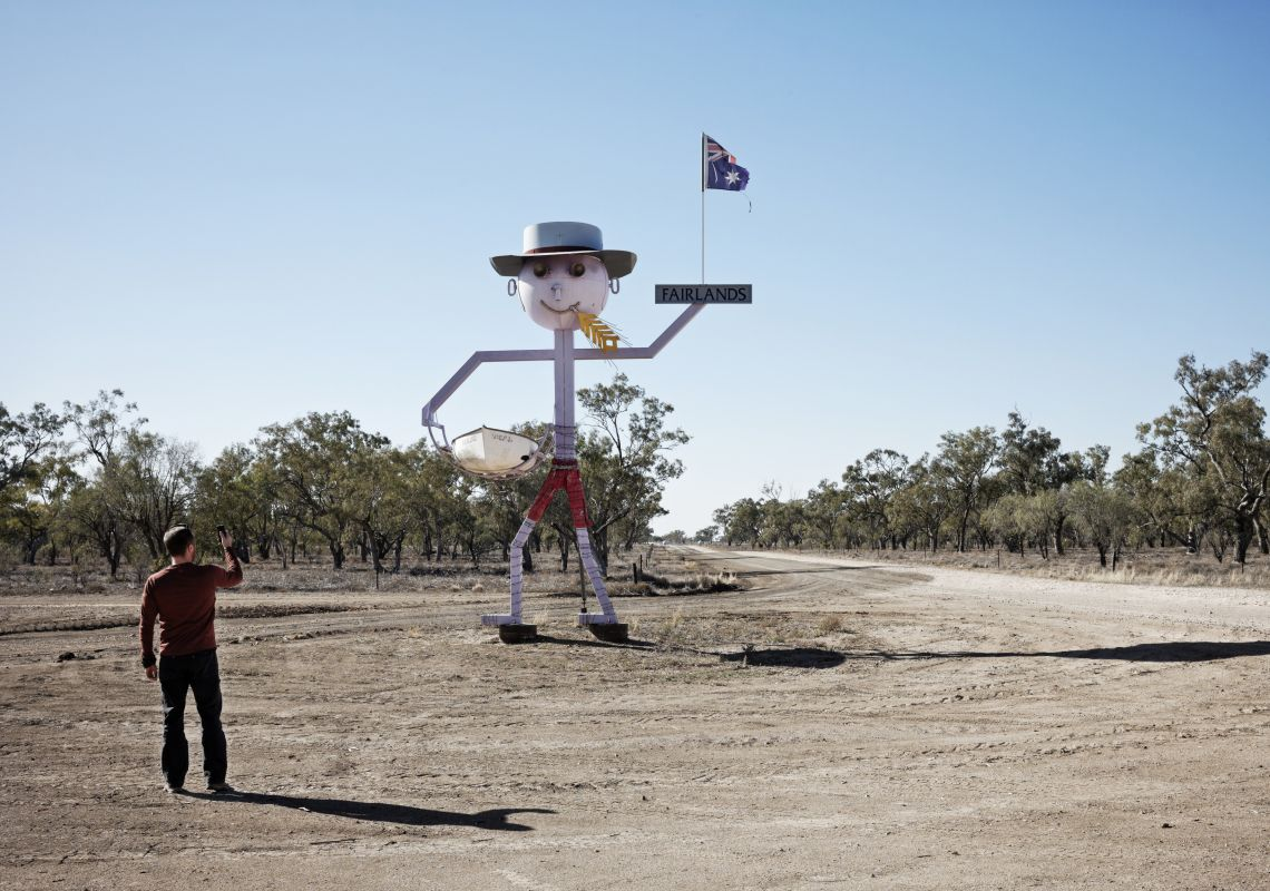 A man takes a photo of a six-metre tall stick figure sculpture of a wheat farmer in Walgett