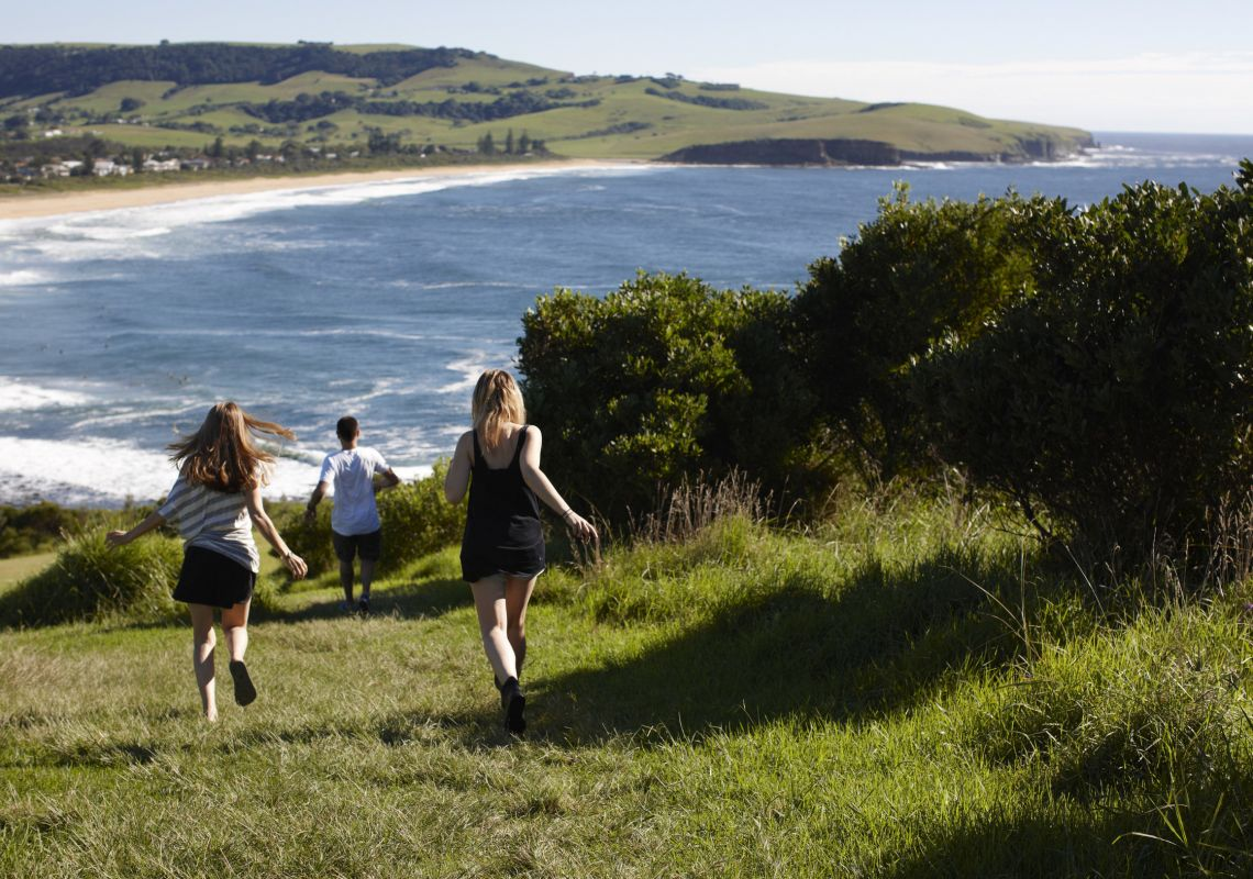 Friends running down to Gerringong beach, South Coast