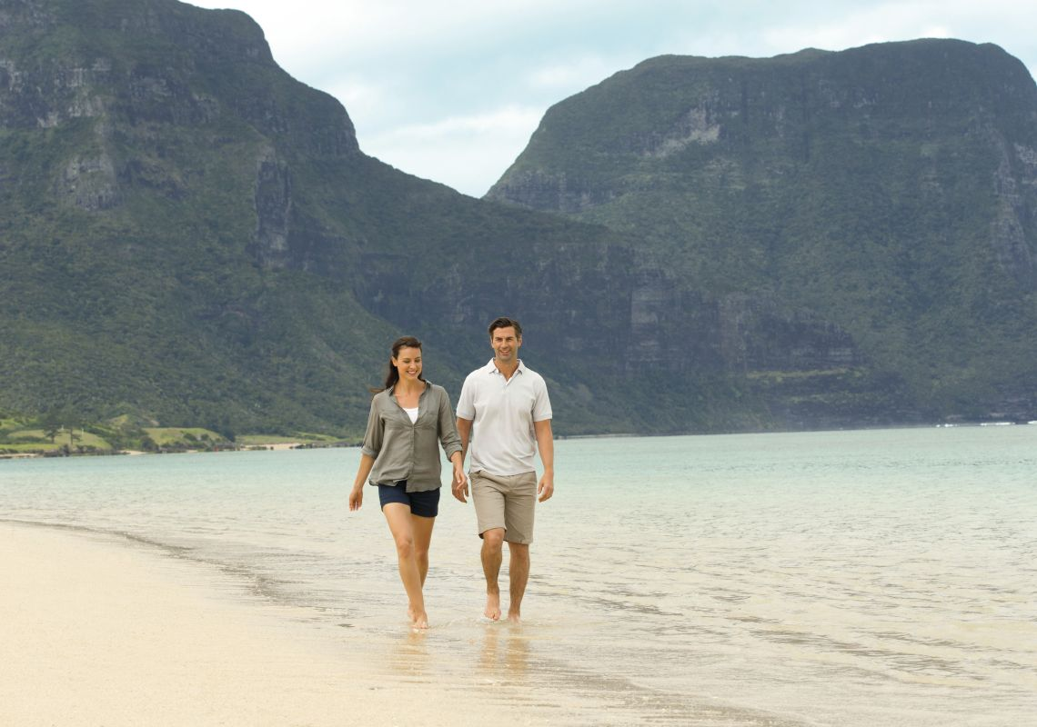 Couple enjoying a relaxing walk along Lagoon Beach on Lord Howe Island with Mount Gower as the backdrop.