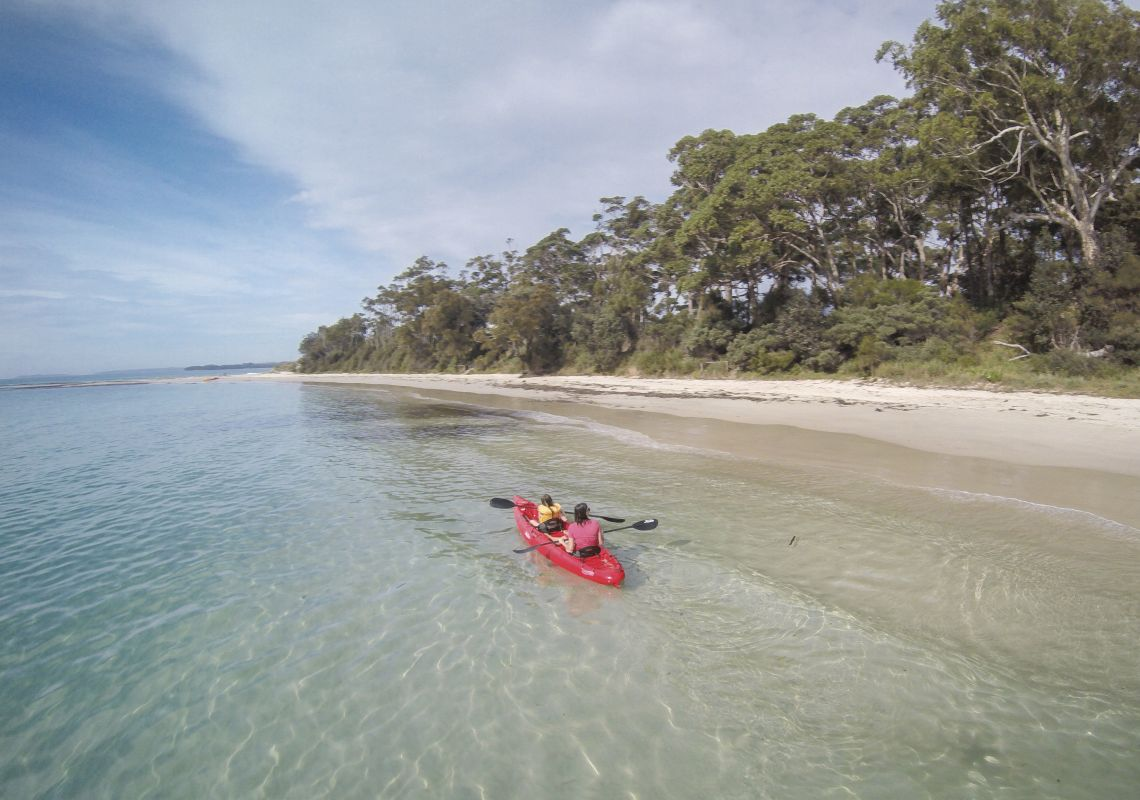 Mother and daughter kayaking along Sailors Beach near Moona Moona Creek in Huskisson, Jervis Bay