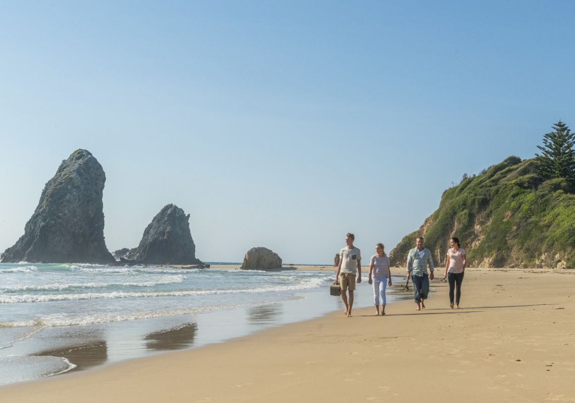 Family walking along the beach ready to fish at Glasshouse Rocks, Narooma