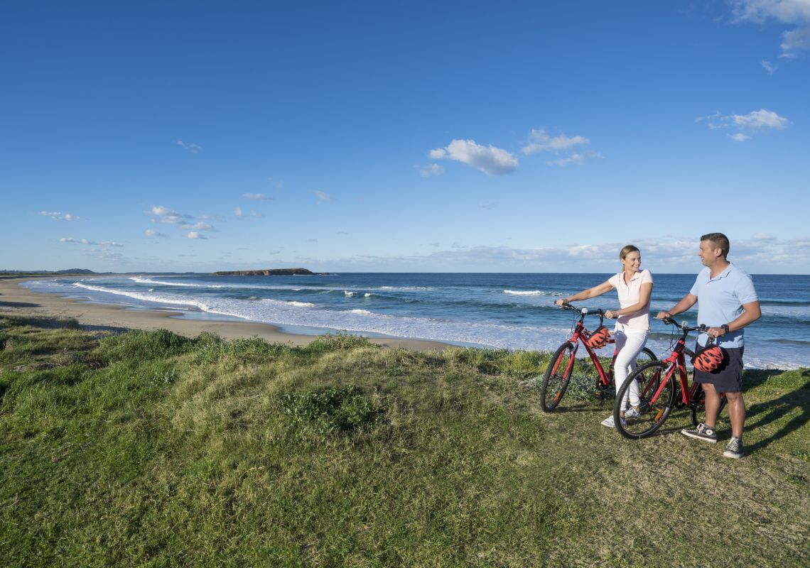 Couple enjoying a cycle in the afternoon by the beach in Shellharbour