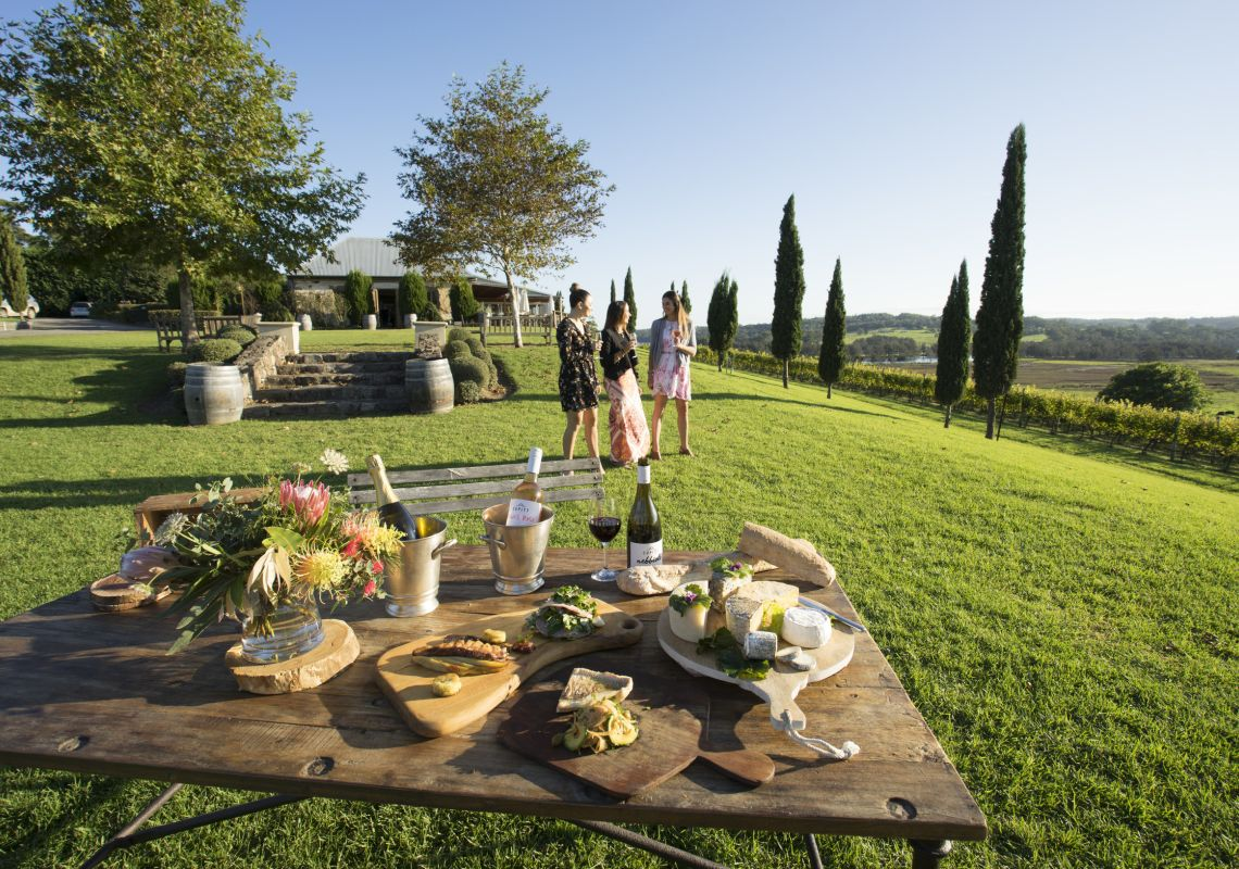 Women enjoying food and drink with scenic views across Cupitt's Winery in Ulladulla