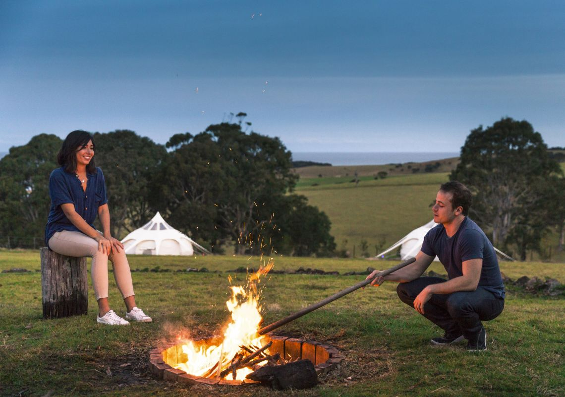 Couple warming up by the fire pit at their Tilba Lake Camp glamping accommodation in Central Tilba