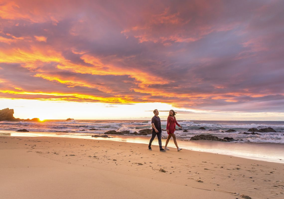 Couple enjoying a morning walk along the beach near Camel Rock, Bermagui
