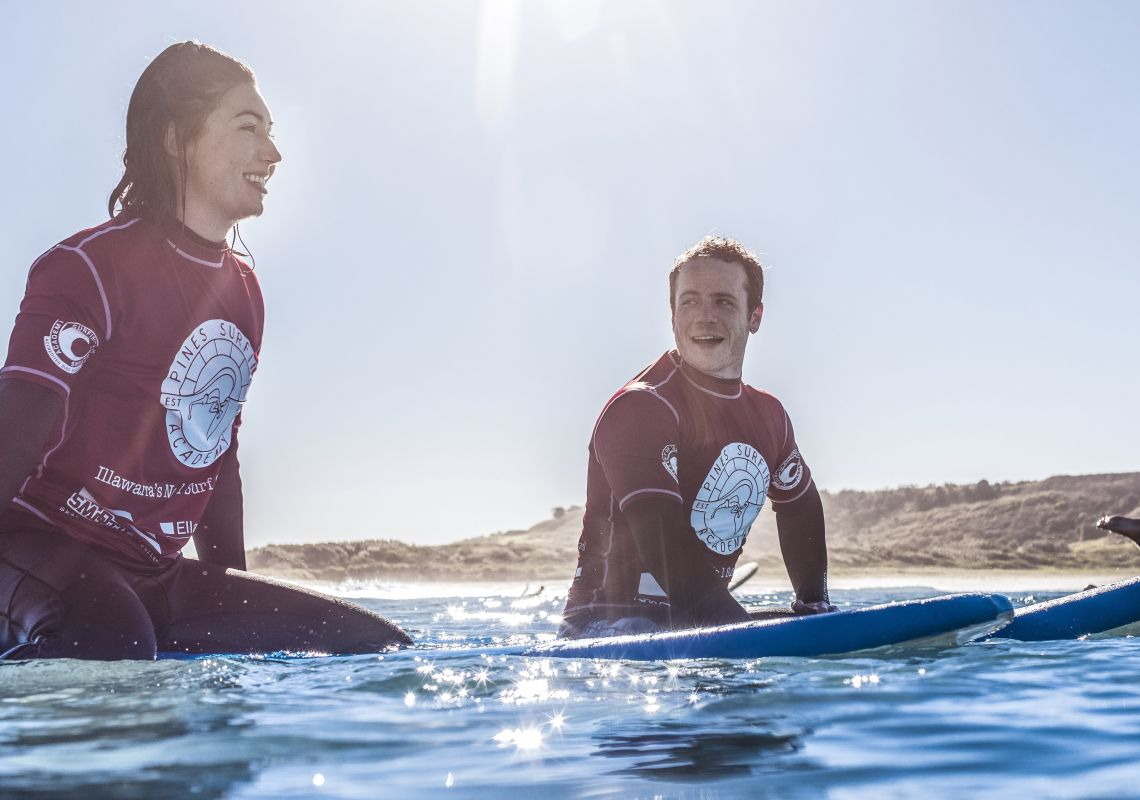 Couple learning to surf with Pines Surfing Academy Surf School at Killalea Beach ('The Farm'), Shell Cove