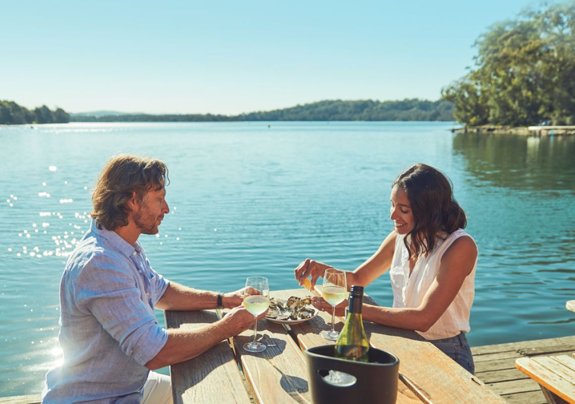 A couple having some Oysters and enjoying of drinking at Tuross Boatshed and Cafet in Tuross Head , Eurobodalla, South Coast